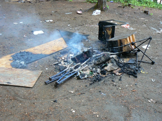 Campfire with burnt chairs and camp stools at Beavertail lake